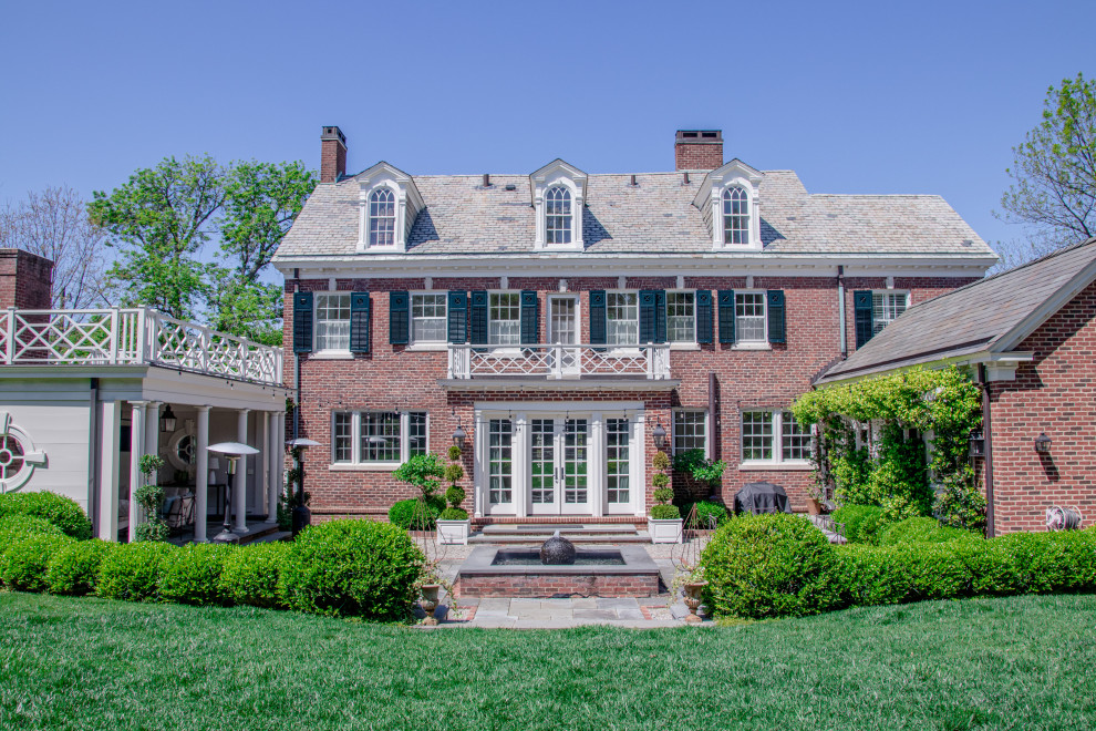 Inspiration for a timeless red two-story brick exterior home remodel in Other with a shingle roof and a gray roof