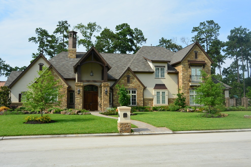 Inspiration for a large rustic multicolored two-story mixed siding house exterior remodel in Houston with a hip roof and a shingle roof