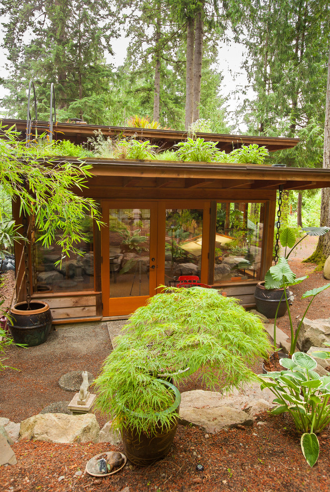 Inspiration for a contemporary one-story wood exterior home remodel in Other with a green roof