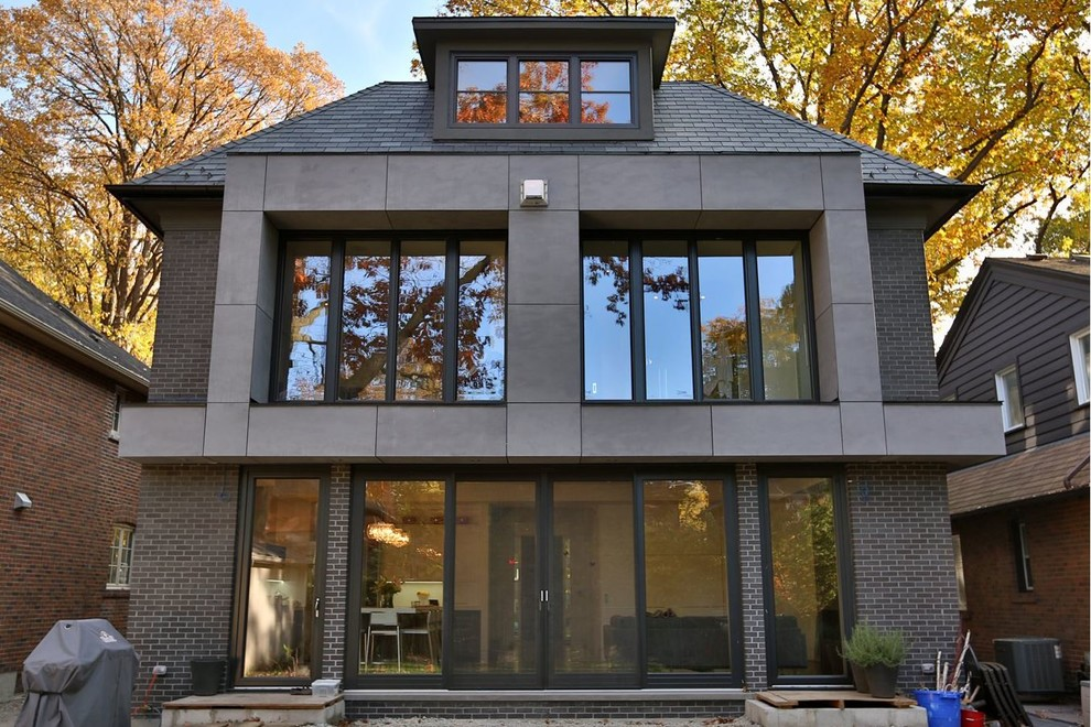 Large contemporary brown two-story brick exterior home idea in Toronto with a hip roof