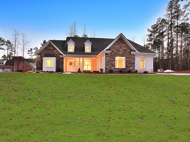 Foto della facciata di una casa beige classica a due piani di medie dimensioni con rivestimento in mattoni e tetto a capanna
