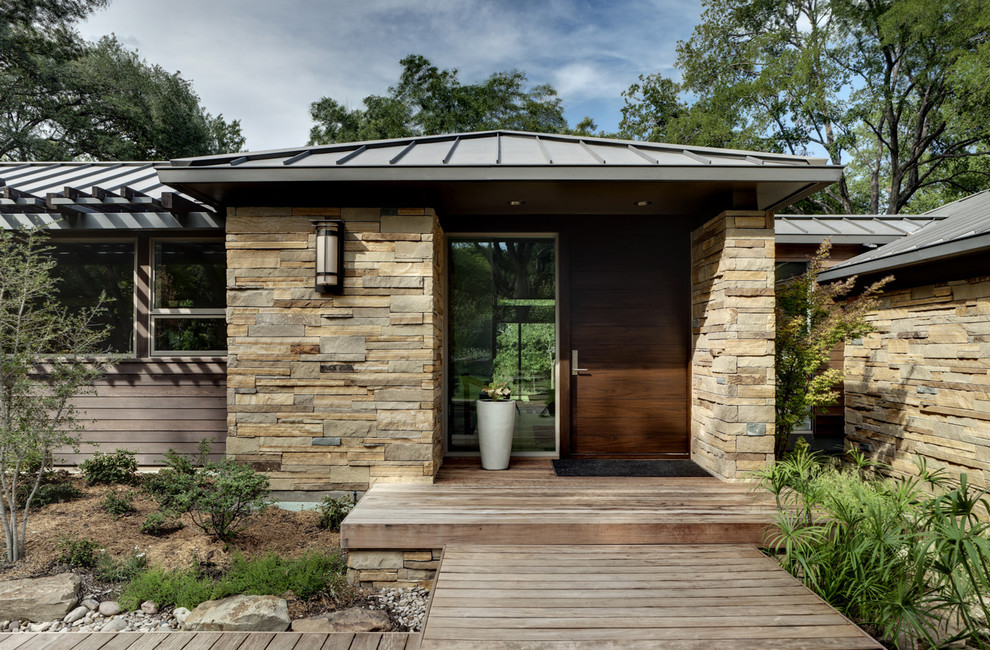 Trendy stone exterior home photo in Dallas with a metal roof