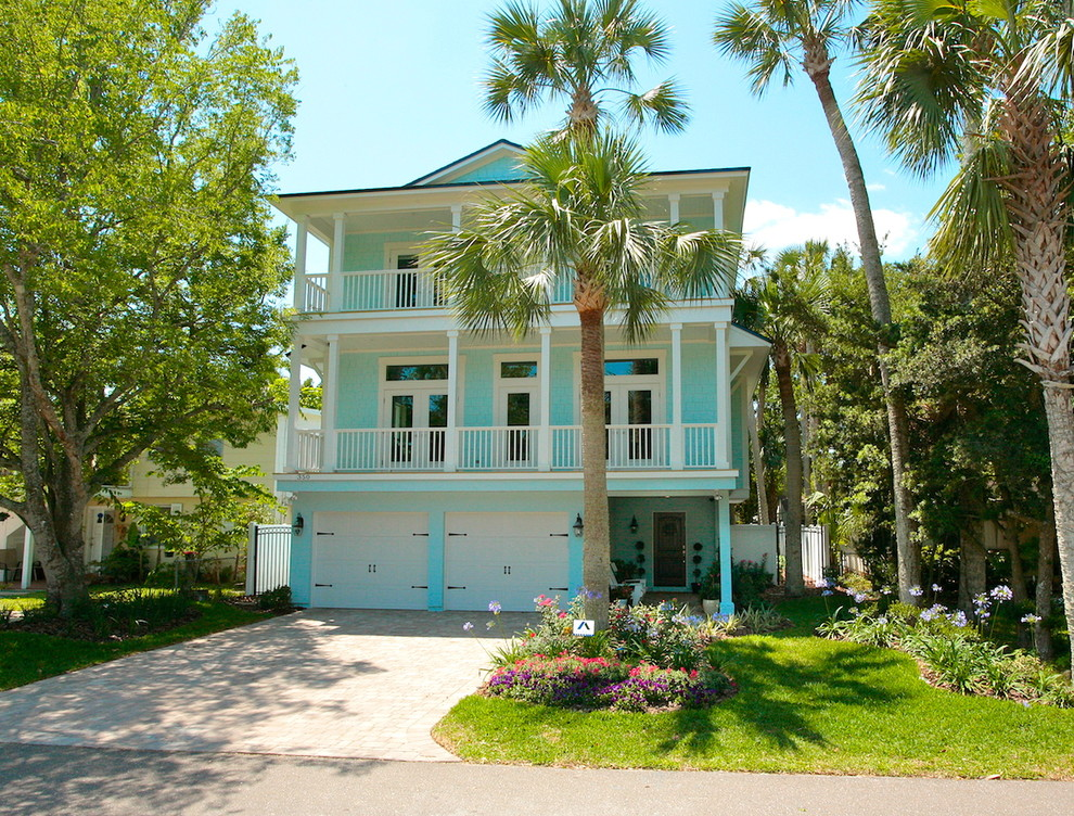 Inspiration for a mid-sized tropical blue three-story wood house exterior remodel in Jacksonville with a shingle roof