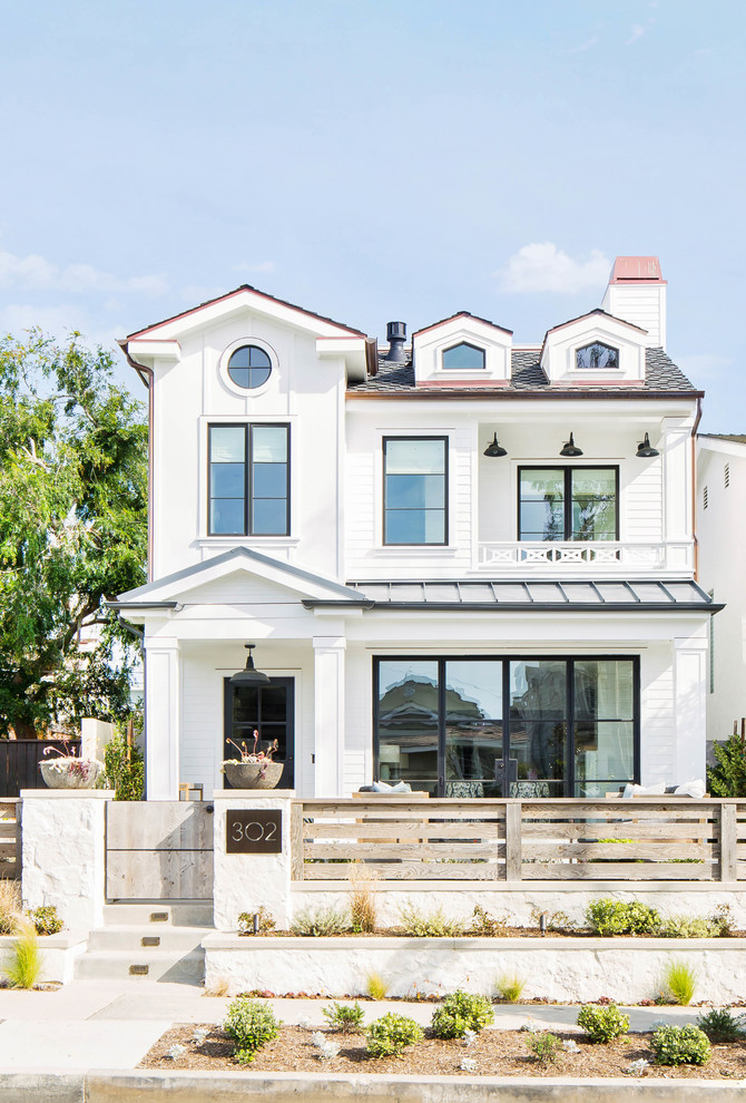 Inspiration for a large country white three-story exterior home remodel in Orange County with a mixed material roof