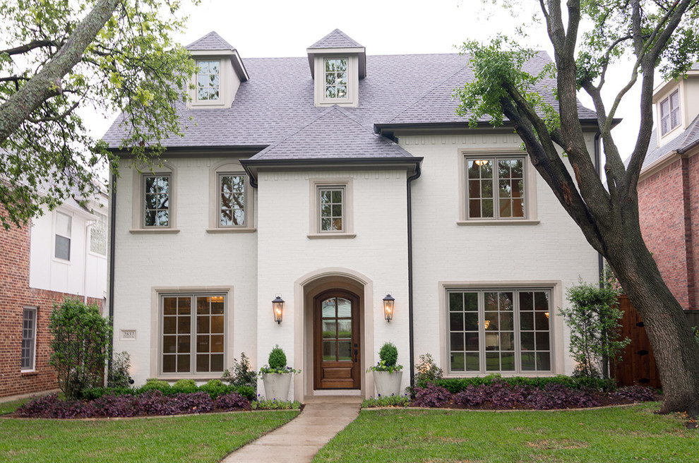 Mid-sized traditional white three-story brick exterior home idea in Dallas