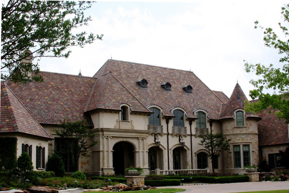 Inspiration for a huge timeless beige two-story stucco house exterior remodel in Dallas with a tile roof