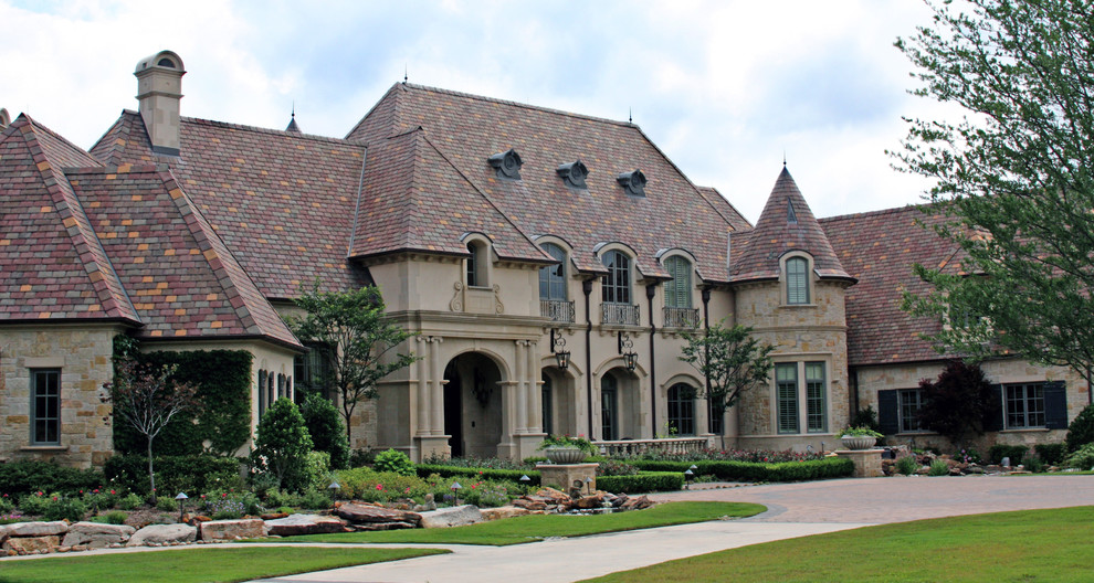 Huge traditional beige two-story stucco house exterior idea in Dallas with a tile roof