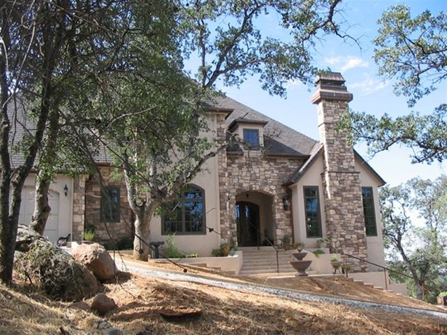 French country home with stone mediterranean exterior for Stucco stone exterior designs