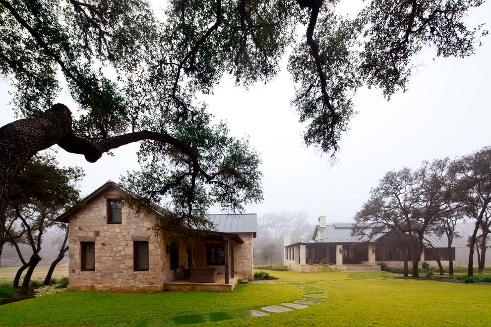 Farmhouse two-story stone gable roof idea in Austin