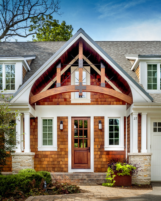Front entry gable detail with rustic arched beams and iron for Craftsman gable