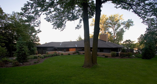 Large 1950s black one-story mixed siding exterior home idea in Minneapolis with a hip roof