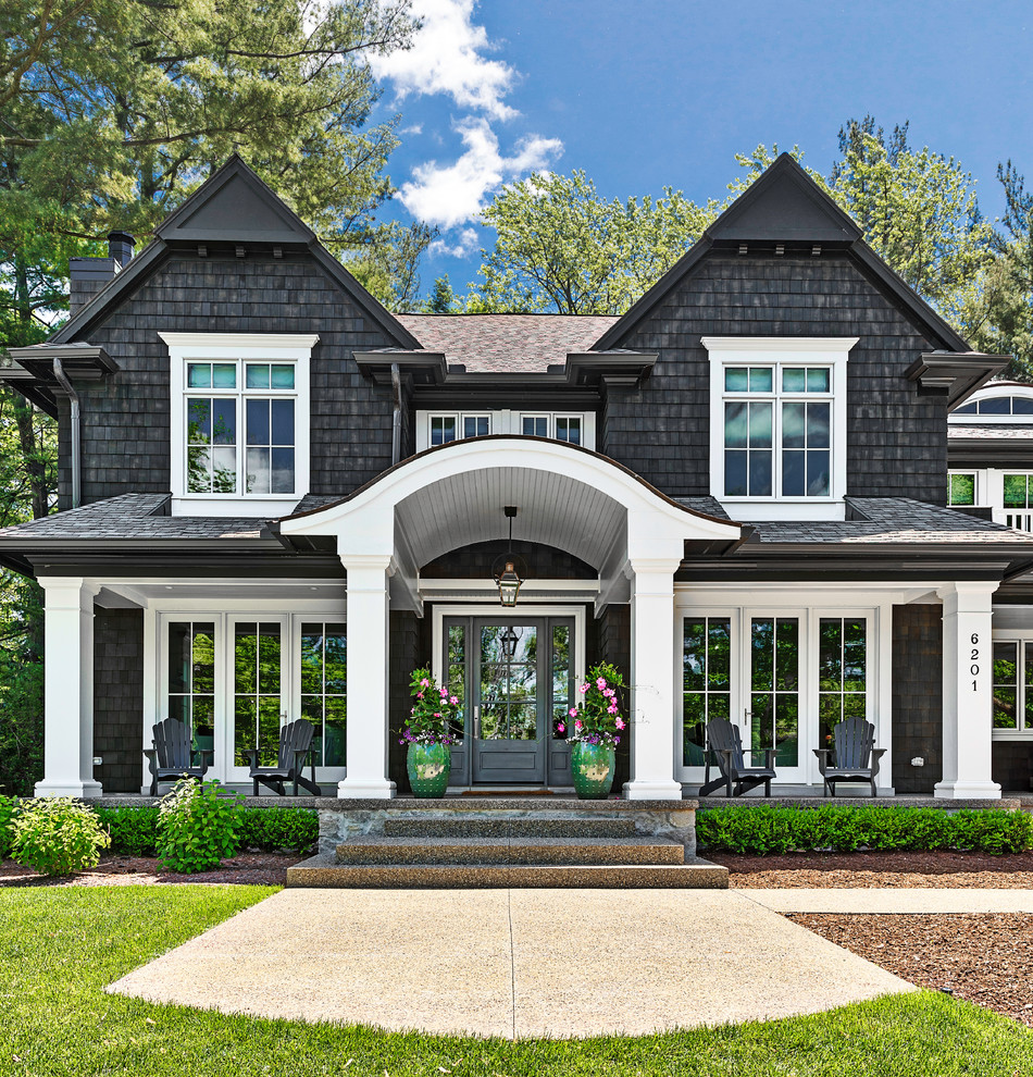 Large beach style black two-story wood exterior home photo in Detroit with a shingle roof