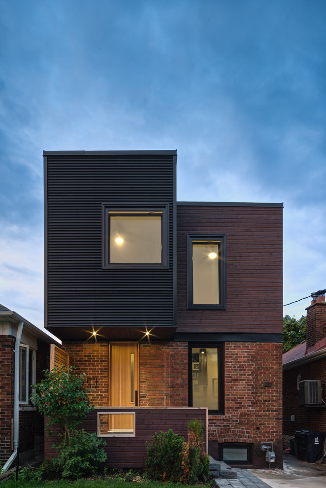 Example of a trendy black two-story mixed siding flat roof design in Toronto