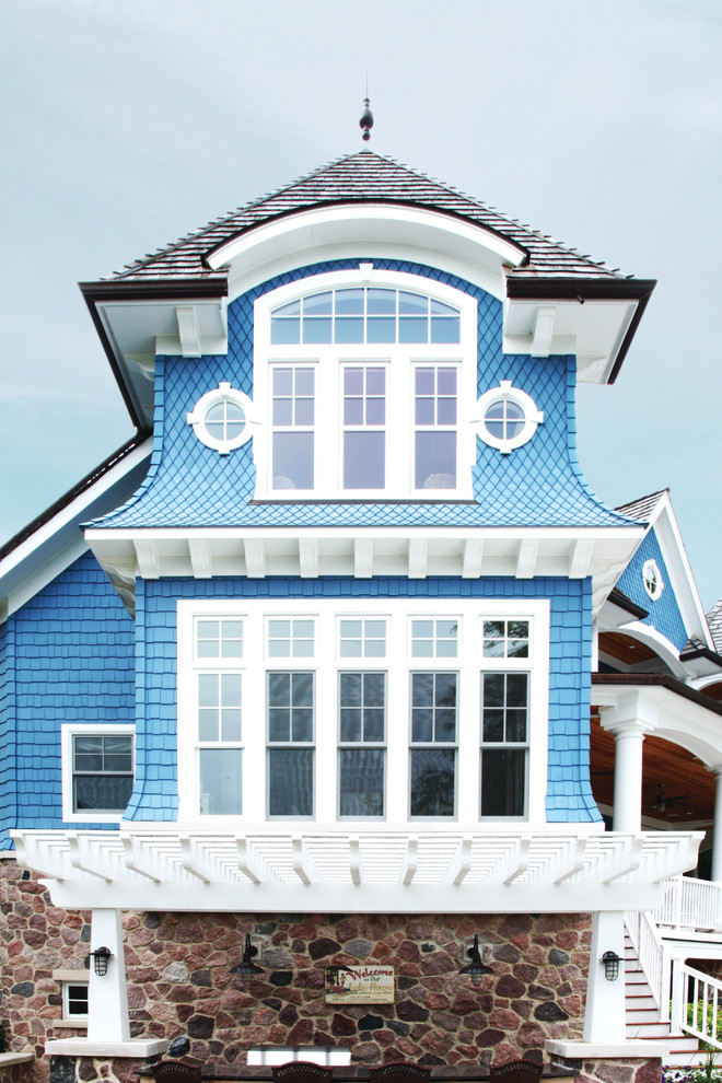 Example of a large beach style blue three-story mixed siding house exterior design in Chicago