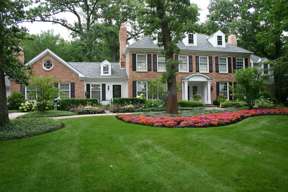 Large traditional red two-story brick exterior home idea in Chicago with a hip roof