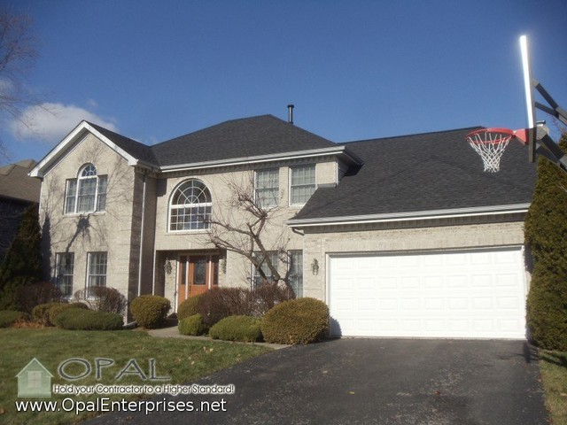 Gray Brick House, GAF Timberline HD Charcoal Shingle Roof And A Wood Front  Door Traditional