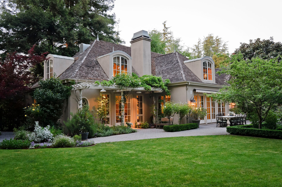 Example of a large tuscan beige two-story stucco exterior home design in San Francisco with a hip roof and a shingle roof
