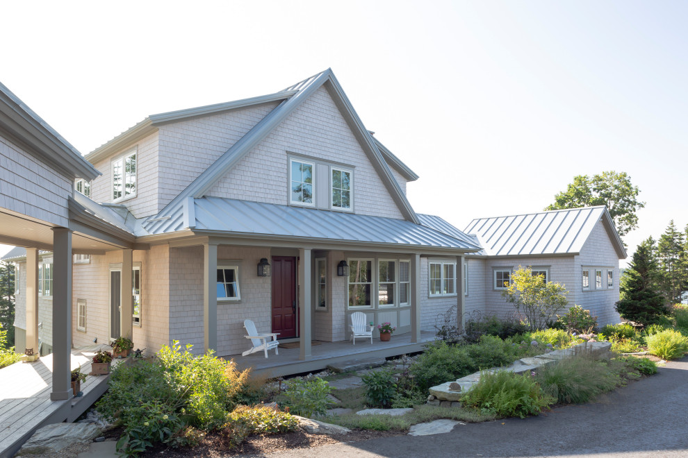 Example of a beach style beige two-story wood exterior home design in Portland Maine with a metal roof