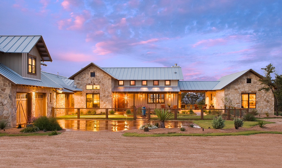 Example of a farmhouse stone exterior home design in Austin with a metal roof