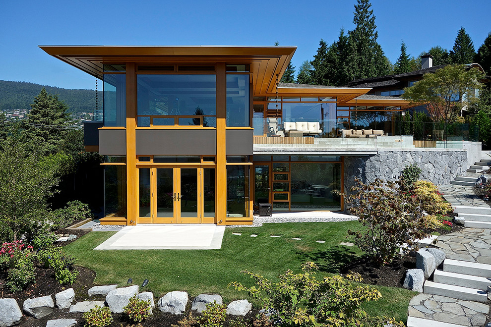 Contemporary two-story glass exterior home idea in Vancouver with a hip roof