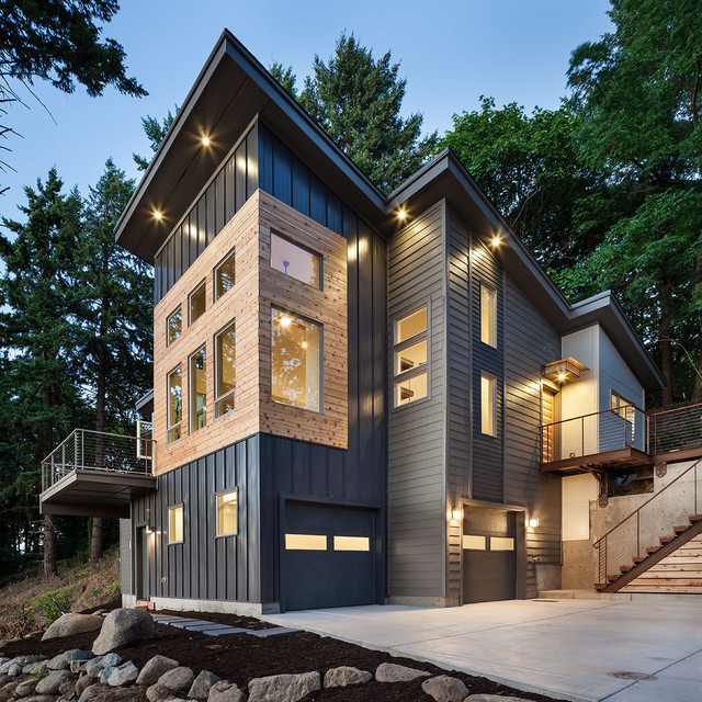 large trendy gray three story metal exterior home photo in portland with a shed roof