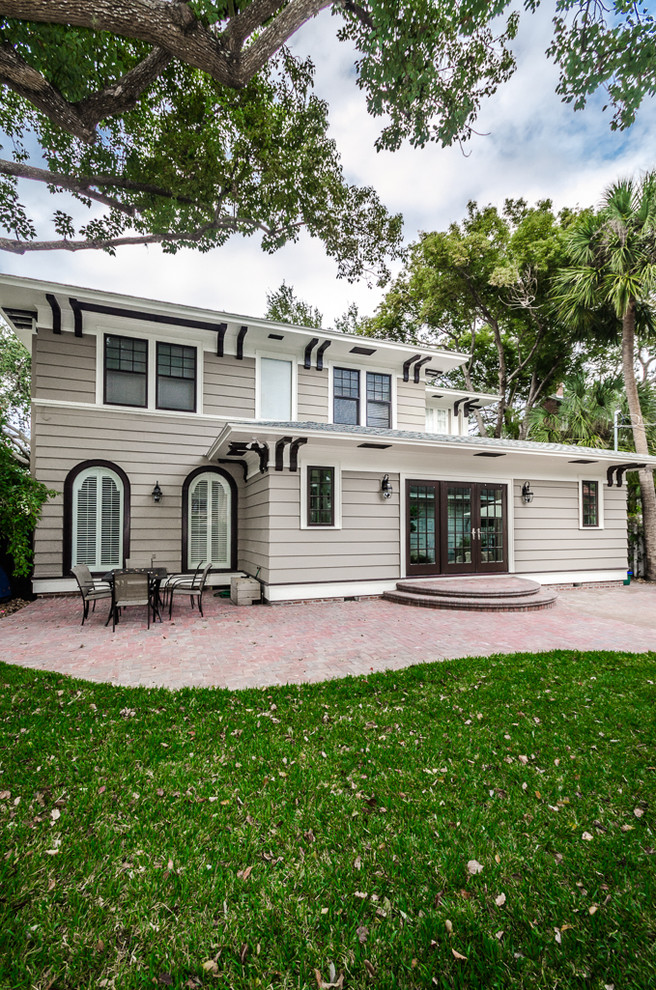 Elegant beige two-story wood exterior home photo in Tampa with a hip roof