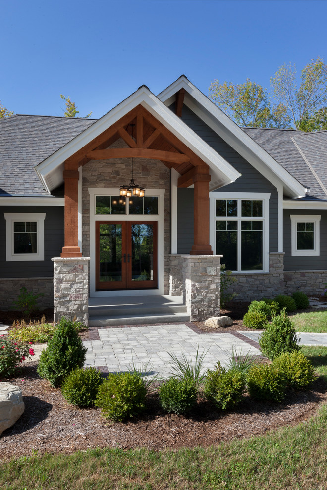 Large arts and crafts gray one-story concrete exterior home photo in Milwaukee with a shingle roof