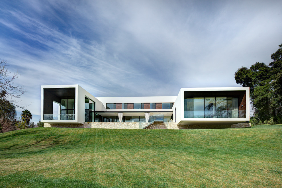 Large minimalist white two-story glass flat roof photo in San Francisco