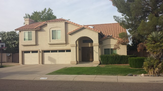 Inspiration for a mid-sized timeless beige two-story stucco exterior home remodel in Phoenix with a tile roof