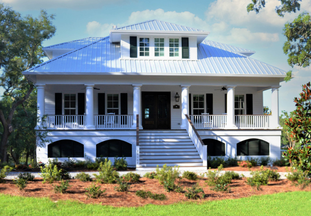 Inspiration for a coastal white three-story wood house exterior remodel in Other with a hip roof and a metal roof