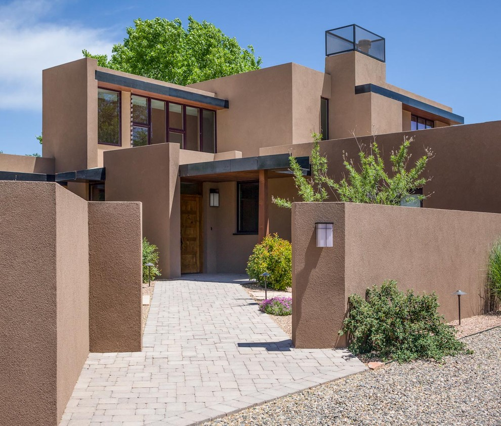 Large southwest brown two-story stucco exterior home photo in Albuquerque with a metal roof