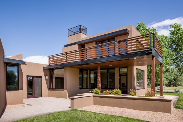 Large southwestern beige two-story stucco exterior home idea in Albuquerque with a metal roof