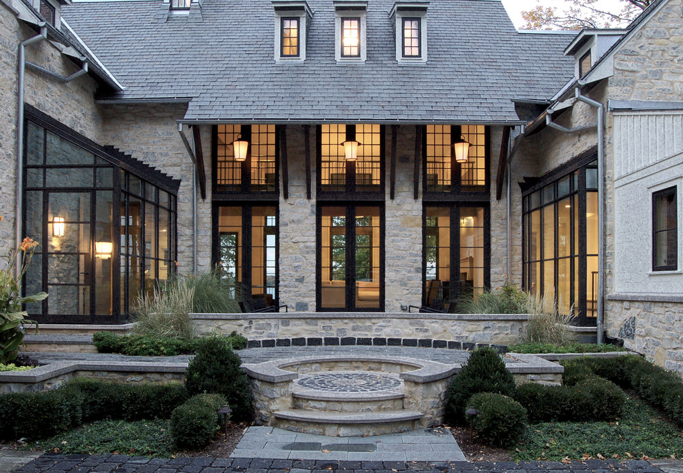 Traditional gray three-story stone exterior home idea in Milwaukee with a hip roof