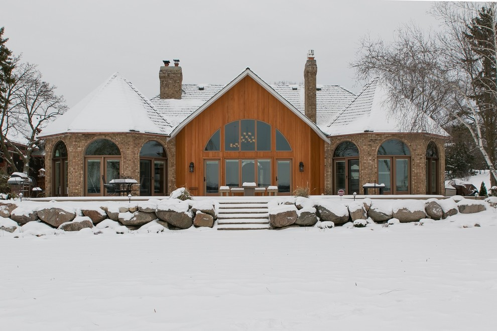 Example of a classic brown one-story mixed siding house exterior design in Minneapolis with a hip roof and a shingle roof
