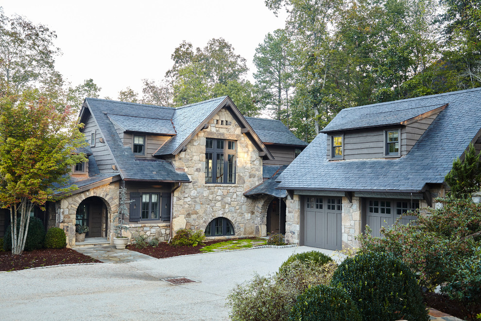 Mountain style beige two-story stone exterior home photo with a shingle roof