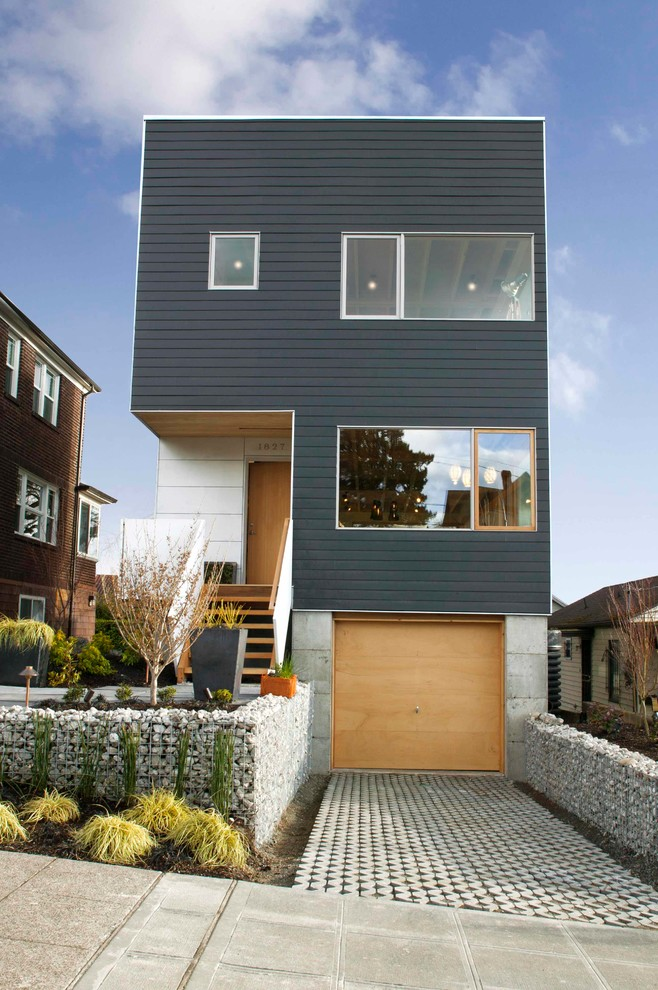 Inspiration for a contemporary black three-story flat roof remodel in Seattle