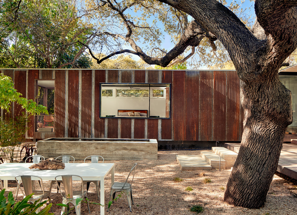 Example of an urban one-story metal flat roof design in Austin
