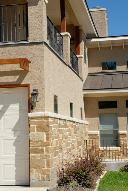 Inspiration for a mid-sized timeless beige two-story stucco gable roof remodel in Austin
