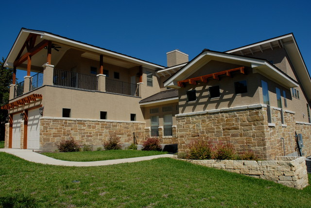 Mid-sized elegant beige two-story stucco gable roof photo in Austin