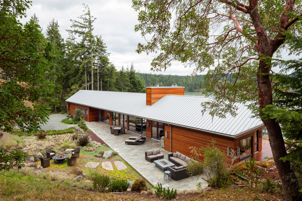 Large contemporary brown split-level wood exterior home idea in Vancouver with a metal roof
