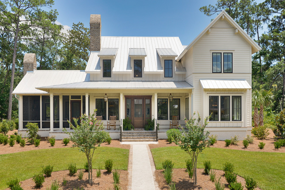 Example of a mid-sized country white two-story wood exterior home design in Other with a metal roof