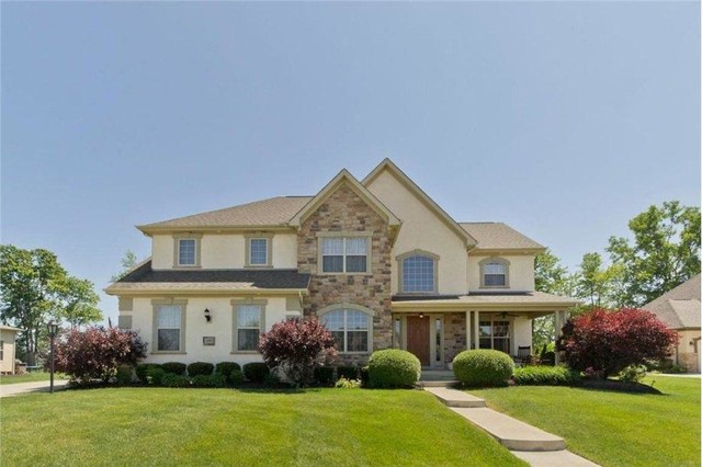 Inspiration for a large timeless beige two-story stone exterior home remodel in Columbus