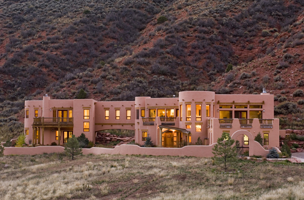 Huge southwest pink two-story adobe exterior home photo in Denver