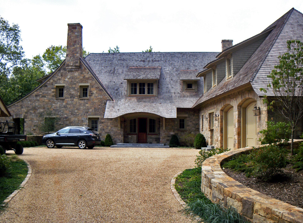 Large elegant two-story stone exterior home photo in Other