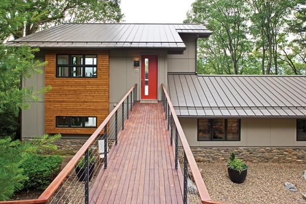 Mid-sized minimalist gray two-story gable roof photo in Other