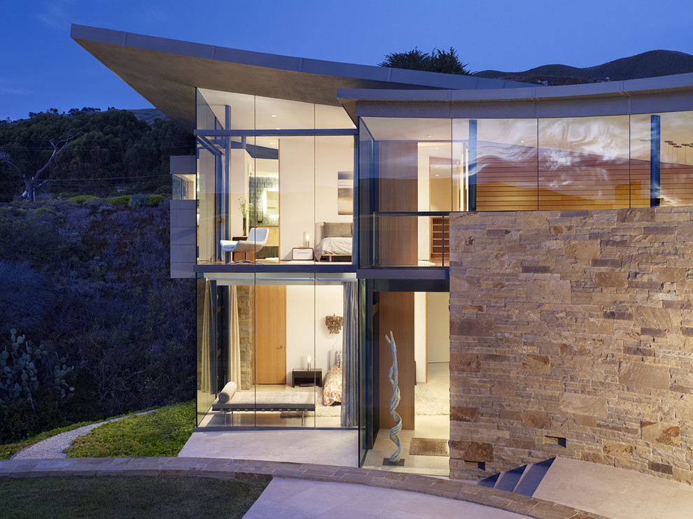 Example of a large trendy two-story glass exterior home design in Other