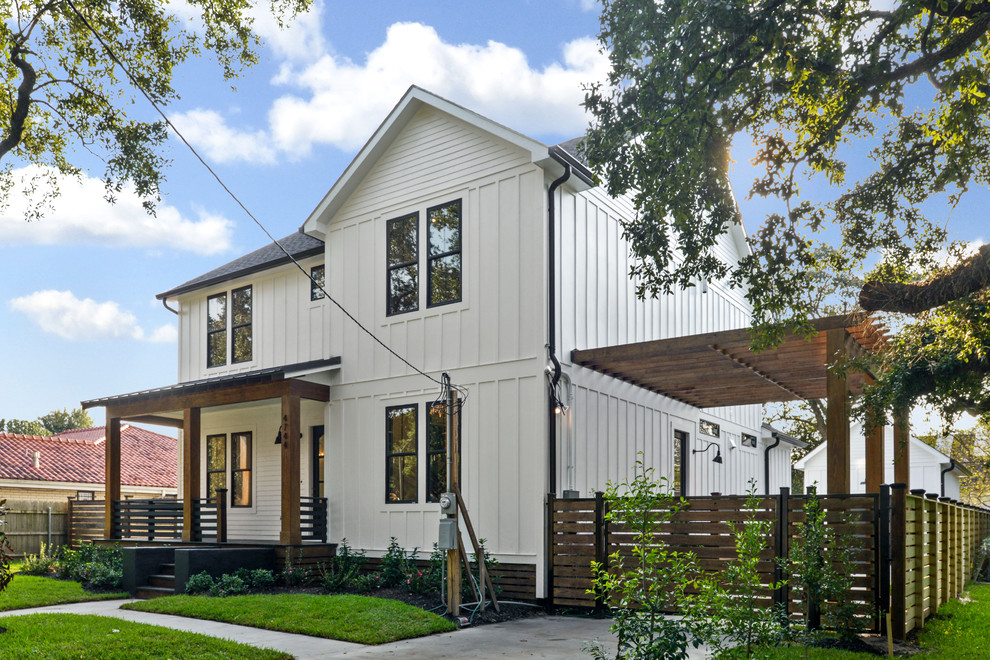 Large country white two-story mixed siding exterior home idea in New Orleans with a mixed material roof