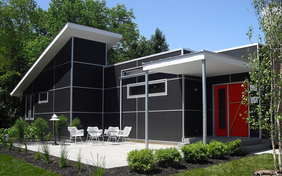 Example of a mid-century modern black one-story exterior home design in Grand Rapids
