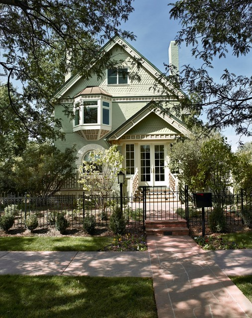Example of an ornate green two-story exterior home design in Denver