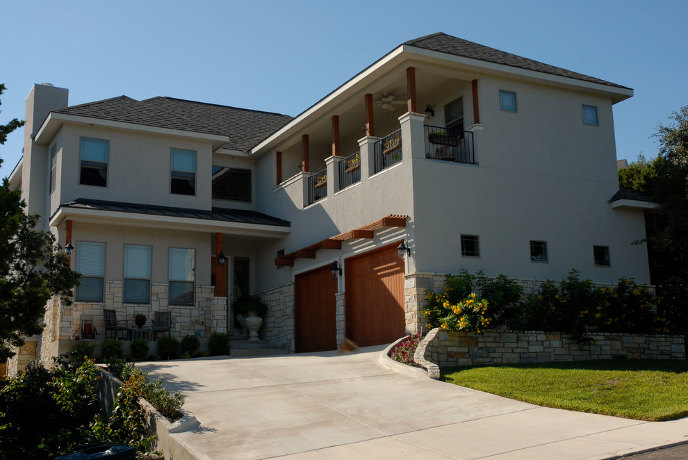 Inspiration for a mid-sized transitional beige two-story stucco exterior home remodel in Austin with a hip roof